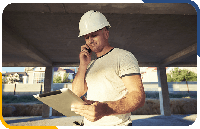 Construction worker having a phone call while on a tablet